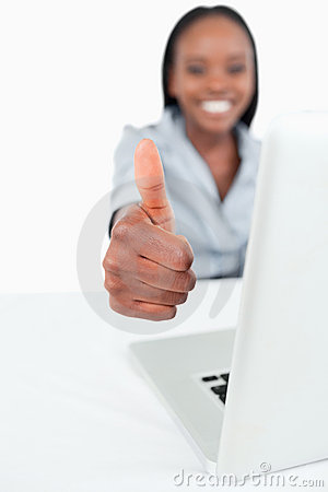 A businesswoman using a laptop with the thumb up