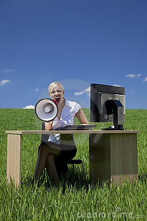 Businesswoman Using Megaphone In A Green Field