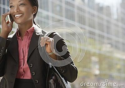 Businesswoman Using Mobile Phone Against Building