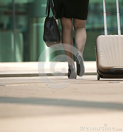 Businesswoman walking with bag and suitcase in the city