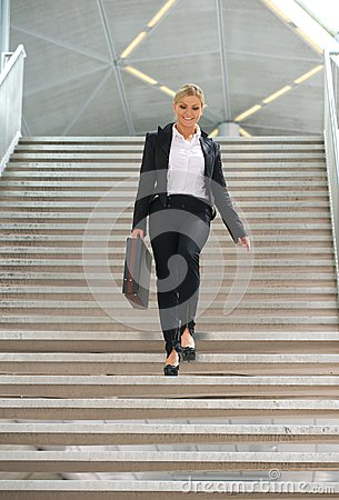 Businesswoman walking downstairs with briefcase