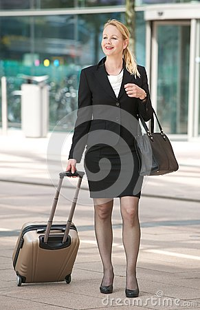 Businesswoman walking with suitcase int he city