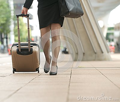Businesswoman walking with travel bags in the city