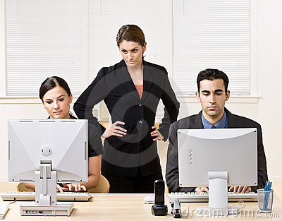 Businesswoman watching co-workers work