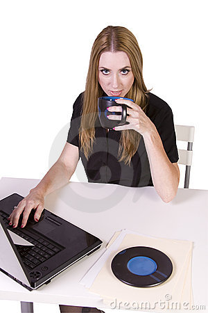 Businesswoman working on laptop with cup of coffee