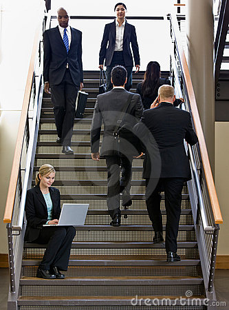 Businesswoman working on laptop on office stair
