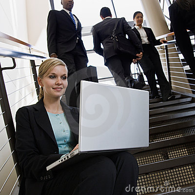 Businesswoman working on laptop on office stairs