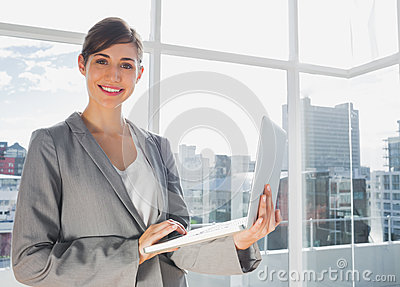 Businesswoman working on laptop and smiling at camera