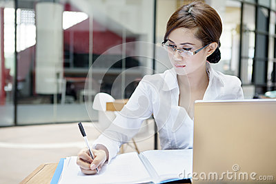Businesswoman writes on a document