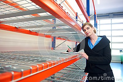 Businesswoman writing on clipboard in warehouse