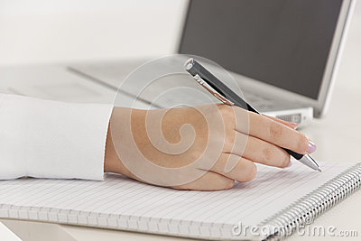 Businesswoman writing on a notebook