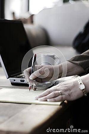 Businesswoman Writing Notes in Hotel Atrium