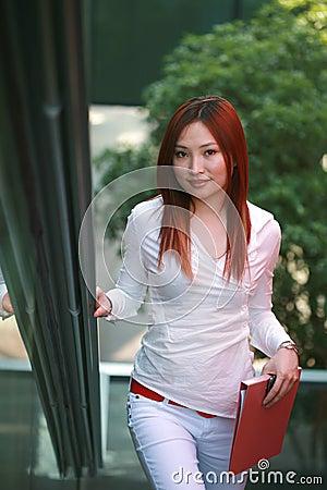 Businesswomen holding folder and wave on escalator