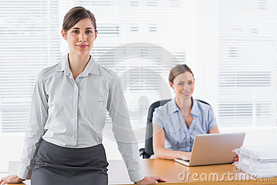 Businesswomen smiling at camera with one sitting and one standin