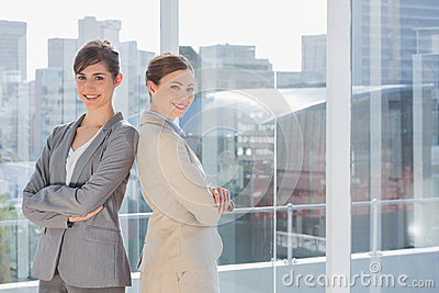 Businesswomen standing back to back