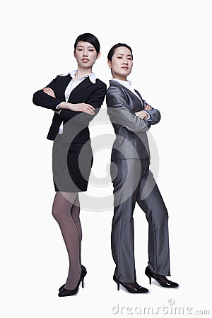 Businesswomen standing back to back and looking at camera, portrait
