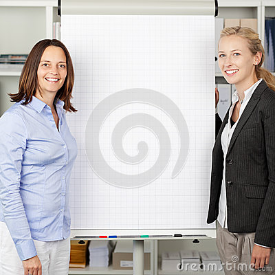 Businesswomen Standing Near Flip Chart