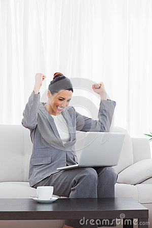 Busineswoman sitting on sofa using laptop cheering