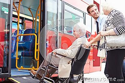 Buss för chaufförHelping Senior Couple bräde via rullstolramp