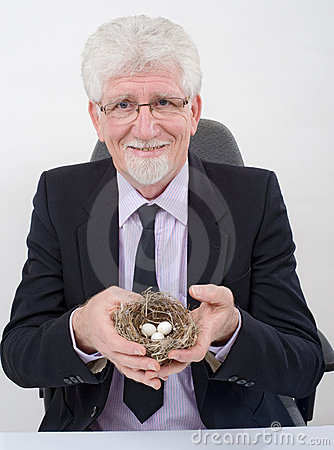 Bussinesman holding a nest with eggs