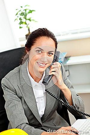 Busy hispanic female architect talking on phone