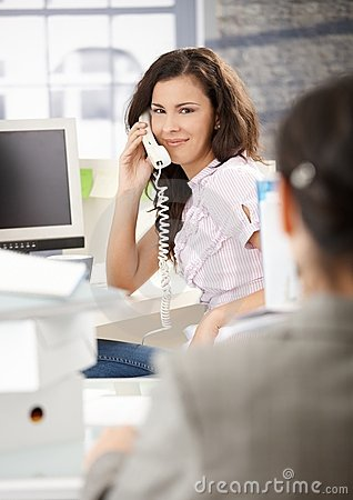 Busy secretary talking on phone in office smiling