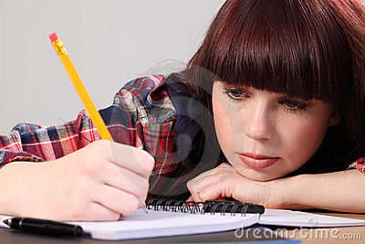 Busy student girl writing homework with pencil