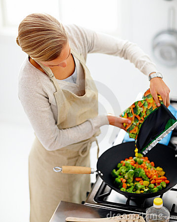Busy woman  cooking vegetables in the kitchen