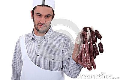 Butcher holding sausages