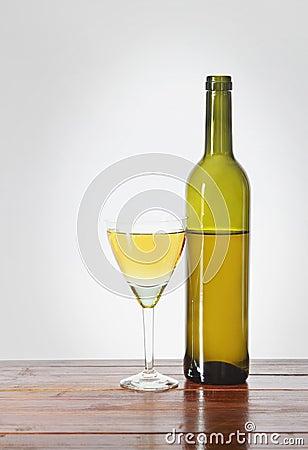 Buteljera och ett exponeringsglas av vin på trätabellen