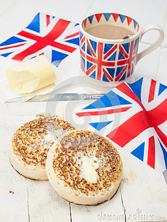 Buttered English crumpets with cup of tea and flag in closeup