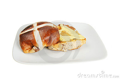 Buttered hot cross bun on a plate isolated against white.