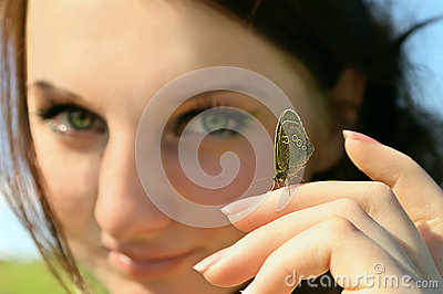 Butterfly on Woman hand with face on background