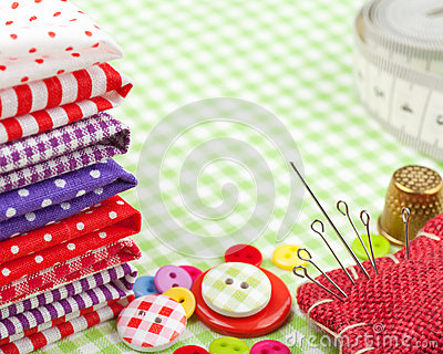 Buttons, colorful fabrics, measuring tape, pin cushion and thimble