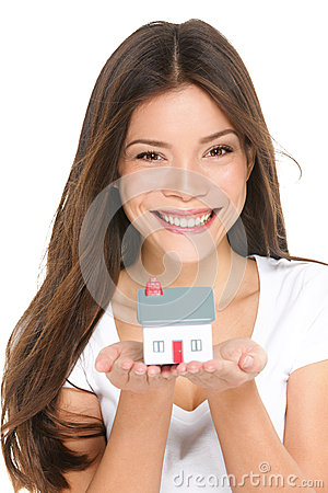 Buying new home concept - woman holding mini house