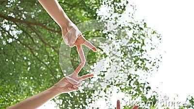 A cámara lenta de ángulo bajo tiró de debajo de un grupo de 5 personas jovenes ponen sus manos juntas sobre el cielo y árboles en metrajes
