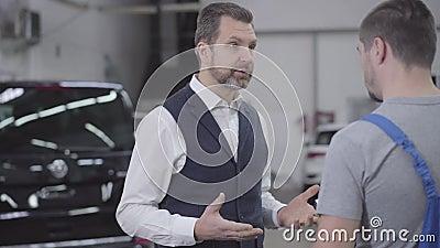 Cámara moviéndose alrededor de dos hombres caucásicos parados al fondo de los autos Cliente irritado hablando con un auto masculi almacen de video