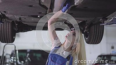 Cámara moviéndose por jóvenes rubios mecánicos caucásicos revisando la parte inferior del automóvil Mujer seria trabajando en el  almacen de metraje de vídeo