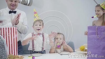 Câmera após o bolo de aniversário para a mesa com a família em chapéus de festa Mãe trazendo tarte com a figura quatro e filho vídeos de arquivo