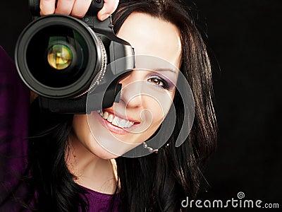Câmera da terra arrendada da mulher do fotógrafo sobre a obscuridade