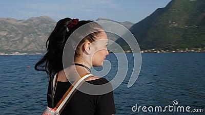 A câmera revolve em torno de uma jovem mulher que admire o mar e as montanhas vídeos de arquivo