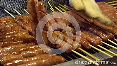 C?mara lenta Gente que cocina asando a la parrilla la salchicha del Bbq en el mercado de la noche de Asia almacen de metraje de vídeo