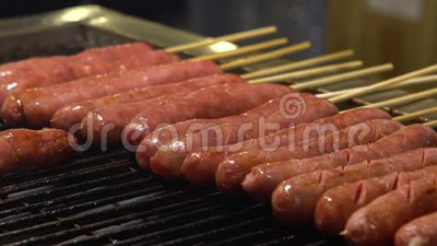 C?mara lenta Gente que cocina asando a la parrilla la salchicha del Bbq en el mercado de la noche de Asia almacen de video