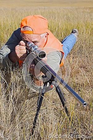 Caçador do rifle na posição propensa
