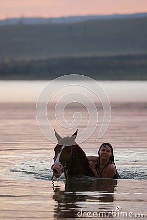 Caballo de la castaña y la muchacha en el agua