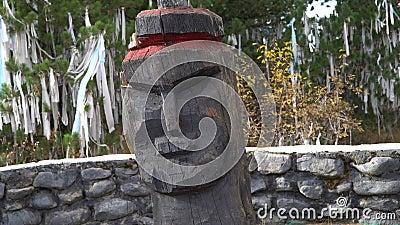 Cabeça velha de madeira pagã sobre fitas rituais sagradas sobre fundo de árvores nas montanhas Altai filme