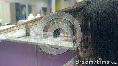 Cabeleireiro que faz molho de cabelo jovem mulher morena cortando cabelos no salão de beleza filme