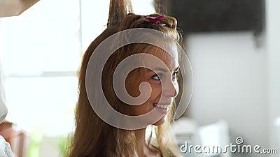Cabeleireiro que faz o cabelo bouffant usando o pulverizador do pente e de cabelo para criar o penteado à mulher bonita no salão  filme