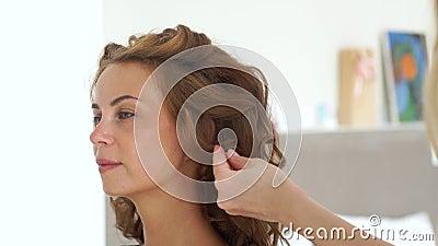 Cabeleireiro que usa a laca ao criar o penteado encaracolado à mulher de cabelos compridos Barbeiro que faz o cabelo de ondulação vídeos de arquivo
