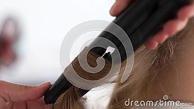 Cabelo de ondulação do barbeiro com tenazes de brasa do cabelo ao criar o penteado à moda no estúdio da beleza Cabeleireiro que u filme